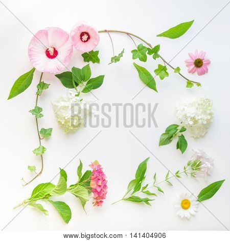 Floral frame with ivy hibiscus and hydrangea flowers on light background. Top view flat lay.