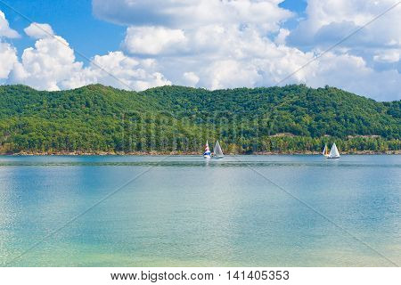 Summer view of a local lake with sailboats and beautiful forest on lake hillside shore in Kentucky USA