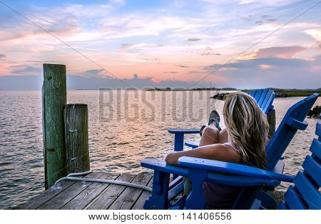 Female sitting in a chair on a pier enjoying a sunset on the Chesapeake Bay
