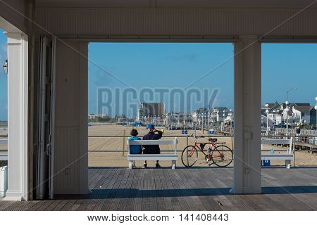 Avon-by-th-Sea NJ USA -- Aug 4 2016 Man and woman sit relaxing on a bench on the boardwalk. Editorial Use Only