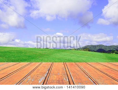 Wood terrace with blurred grass and blue sky background and copy space