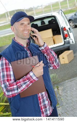 a picture of a happy deliveryman holding box and cellphone