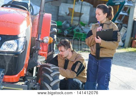 mechanicians examining tractors engine