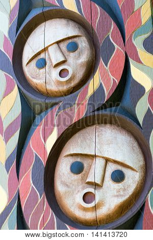 Vancouver Canada - July 24 2016: One of nine totem poles at Hallelujah point in Stanley Park. Portrait of two pastel colored wooden masks on arch. Circular format flame pattern.