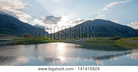Snake River Under Cumulus Cloud Sky In Alpine Wyoming Usa