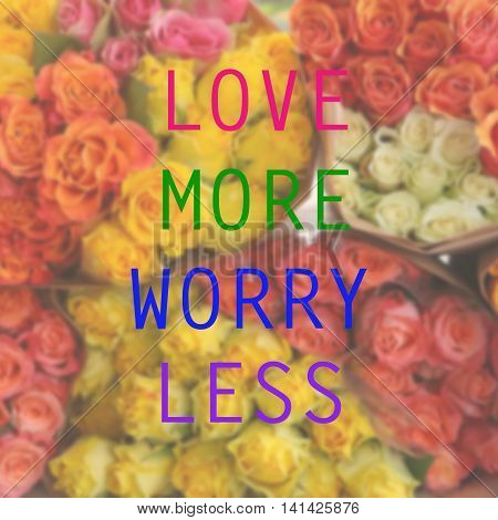 Inspirational quote on blurred flower background...Love more worry less
