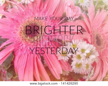 Inspirational quote on blurred flower background....Make your day brighter than yesterday