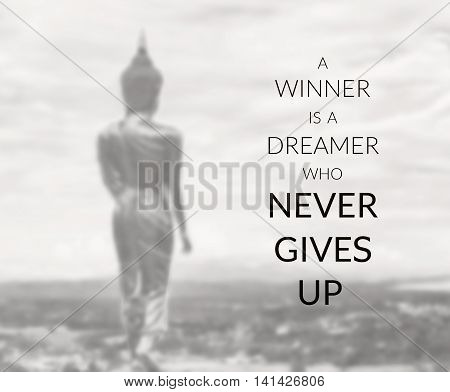 Inspirational quote on blurred background ...a winner is a dreamer who never gives up
