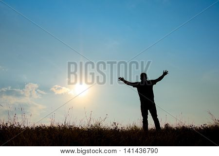 Silhouette of man worship with hands raised to the sky in nature concept of praise worship religion