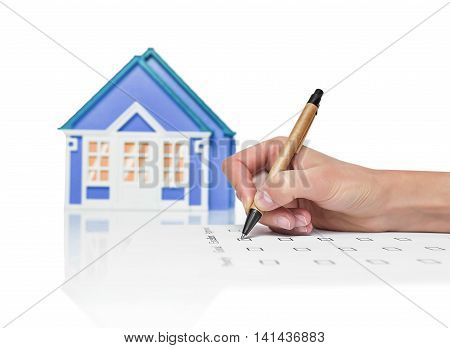 Image of a female signing a deed of sale, mortgage document or insurance contract on a house with a closeup view of his hand with a small model of a house.