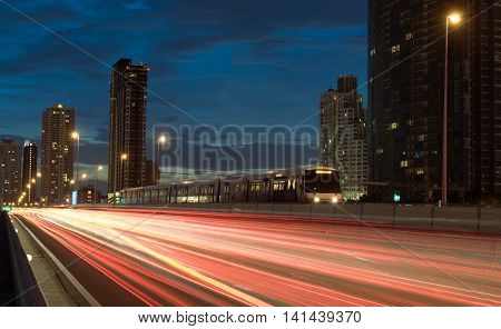 electric train with light trails on the highway at twilight light. train against the backdrop City.