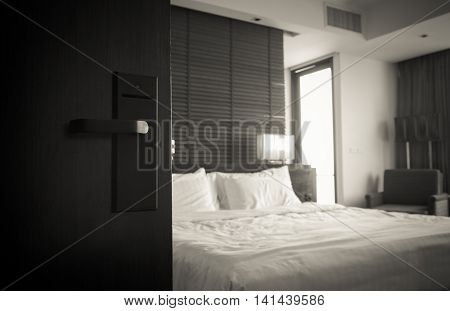 Open the door of the luxury modern hotel room. Black and white tone.