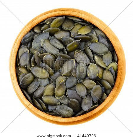 Pepita pumpkin seeds in a bowl on white background. Flat green edible summer squash seeds of Cucurbita pepo, genus Cucurbita, in wooden bowl. Isolated macro photo from above. Close up. Cucurbitaceae.