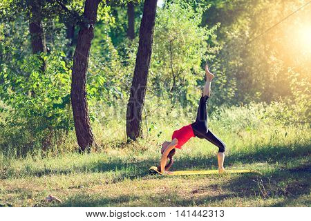 Woman doing strength exercises at outdoor. Smiling happy doing yoga stretches after running. Fitness model outside in green park on summer day.