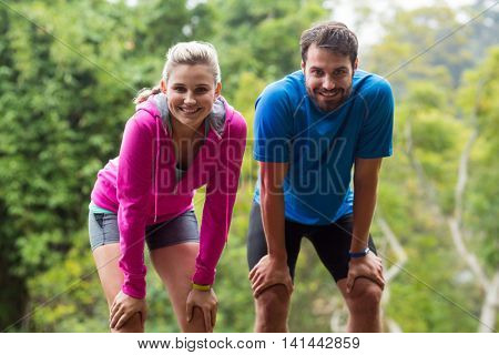 Tired couple taking a break while jogging in forest