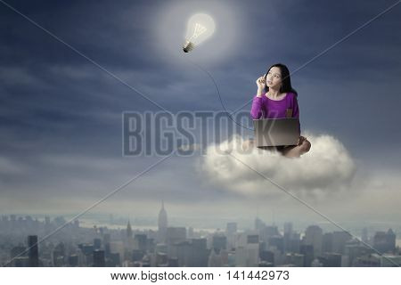 Female college student sitting on the cloud while using laptop computer and looking at a lightbulb