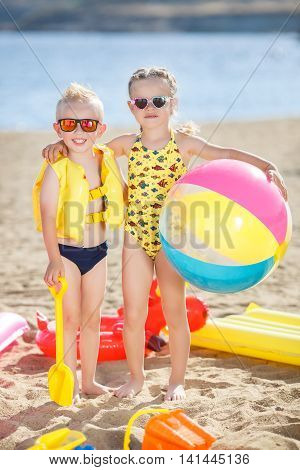 Little girl with pigtails and a little blonde boy with short hair, a brother and sister, both wearing sun glasses, posing together on the beach, standing barefoot on the sand with a big inflatable multi-colored ball against a blue ocean