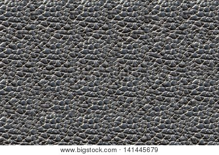 Texture pig skin of natural tanned and processed leather for the manufacture of products. Background skin a dimpled black. Raw materials for industry and leather goods.