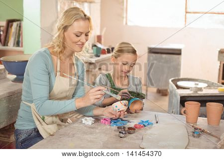 Smiling female potter and girl painting in pottery workshop