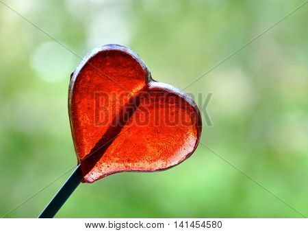 Heart-shaped red lollypop on a green background