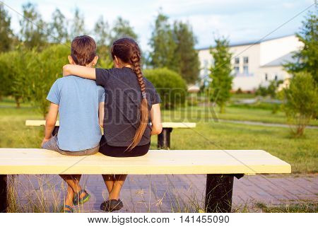 boy and girl embrace. children are sitting on a park bench and hugging. back view. the concept of friendship