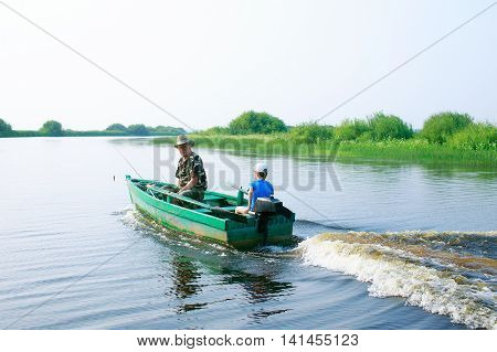 boy and his grandfather drives a motor boat. child skillfully controls a motorboat. fishing with grandpa