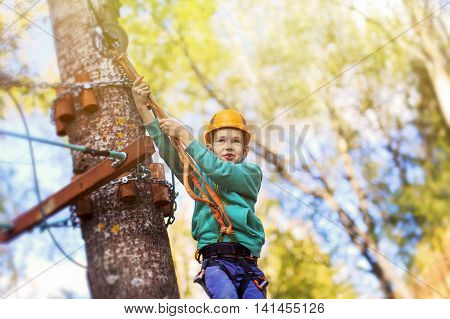 kid ready to zip line flight in adventure park. ziplining. brave child is ready to jump from a height. empty space for your text poster