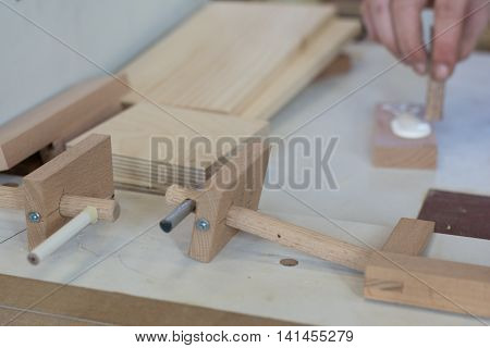 Carpenter working with glue and manufactures wood joints
