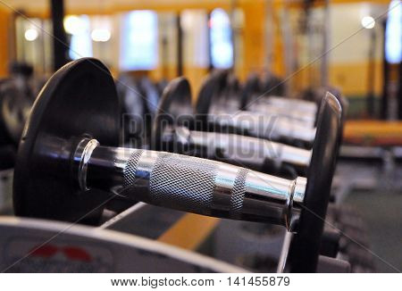 Big dumbbell in fitness and gym room interior sport object