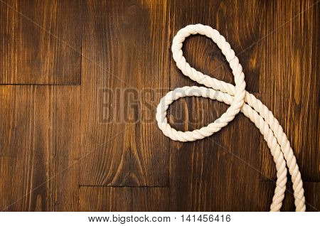 Jute rope in heart shaped on wooden background