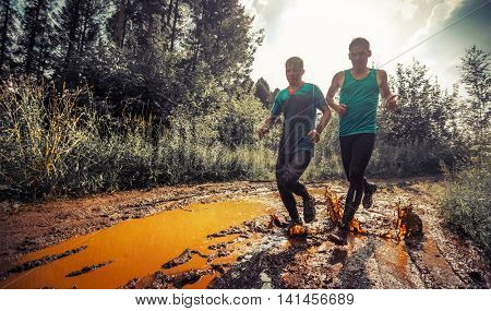 Two trail running athletes running in the forest and crossing the dirty puddle