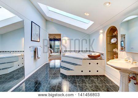 Master Bathroom With Blue Marble Tile Floor And Corner Bath Tub.