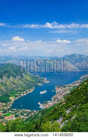 Bay of Kotor (Boka Kotorska) winding bay of the Adriatic Sea in southwestern Montenegro. Vertical airview above Lovcen mountain with cruise large ship and blue simmer sky.