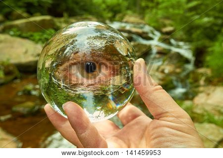 A hand holding a crystal ball on a creek.
