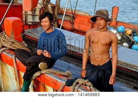 Hua Hin Thailand - December 31 2009: Two Thai fishermen on deck of their boat docked at the Hua Hin public fishing pier