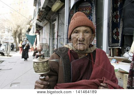 Old buddhist Monk (Lama) rotating prayer wheel on the road in Ladakh India.