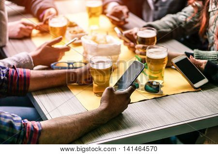 Closeup of hands social networking with mobile phones - Wifi connected multiracial people in bar table meeting - Concept of teamwork and technology addiction concept - Focus on left bottom phone