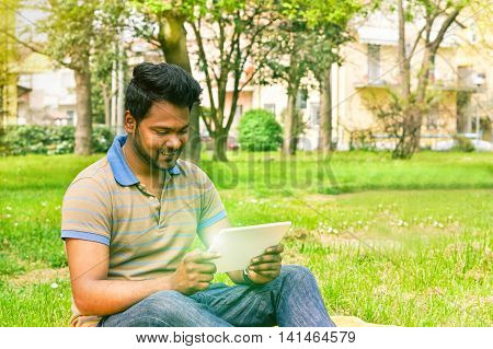 Young indian man having video call on tablet in park university camp - Concept of new technology miracle addiction - Soft warm saturated filter