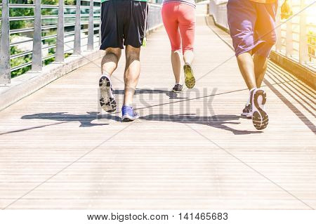 Multiracial runners doing jogging on city contest with sunset - Fitness people training outdoors for a healthy lifestyle - Concept of athlete running for sport competition - Focus on center shoes