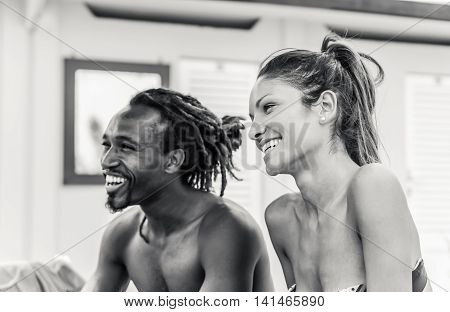 Cheerful multiracial couple smiling on beach for summer vacation - Happy people having fun outdoor - Black and white editing - Happiness and love concept - Soft warm filter with focus on girl's face