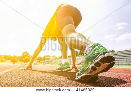 Runner training on athletic running track - Young athletic man ready to sprint outdoor in sport camp - Close up on shoe with back lighting - Soft warm filter with sun halo flare