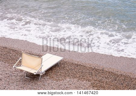canvas chaise lounge left by the sea on the coast of pebbles