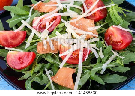 Salmon salad on black plate with green leaves and cherry tomatoes