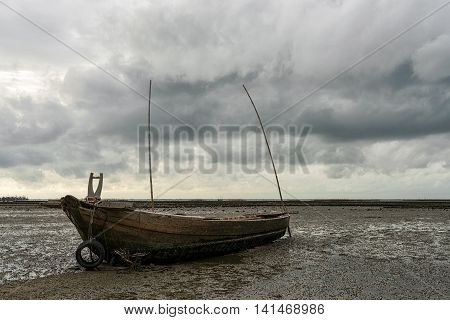 Rowing boat in the sea with rain clouds background.