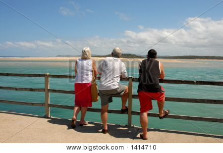 Three People Staring Out To Sea