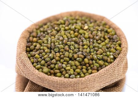 Close up o mung bean in sack bag on white background isolated.