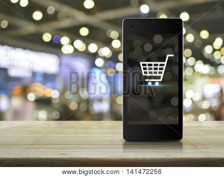 Shopping cart Icon on modern smart phone screen on wooden table over blur light and shadow of mall Shop online concept