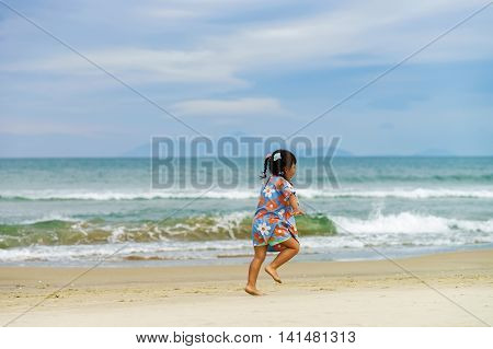Danang, Vietnam - February 20, 2016: Girl running along the China Beach in Danang in Vietnam. It is also called Non Nuoc Beach. South China Sea on the background.