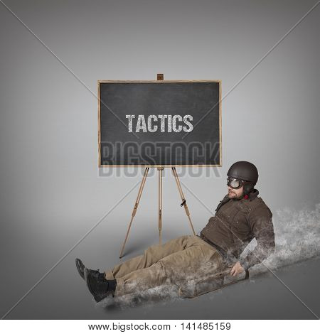 Tactics text on blackboard with businessman sliding with a sledge