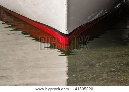 Red Bow of Boat at Waterline in shallow water